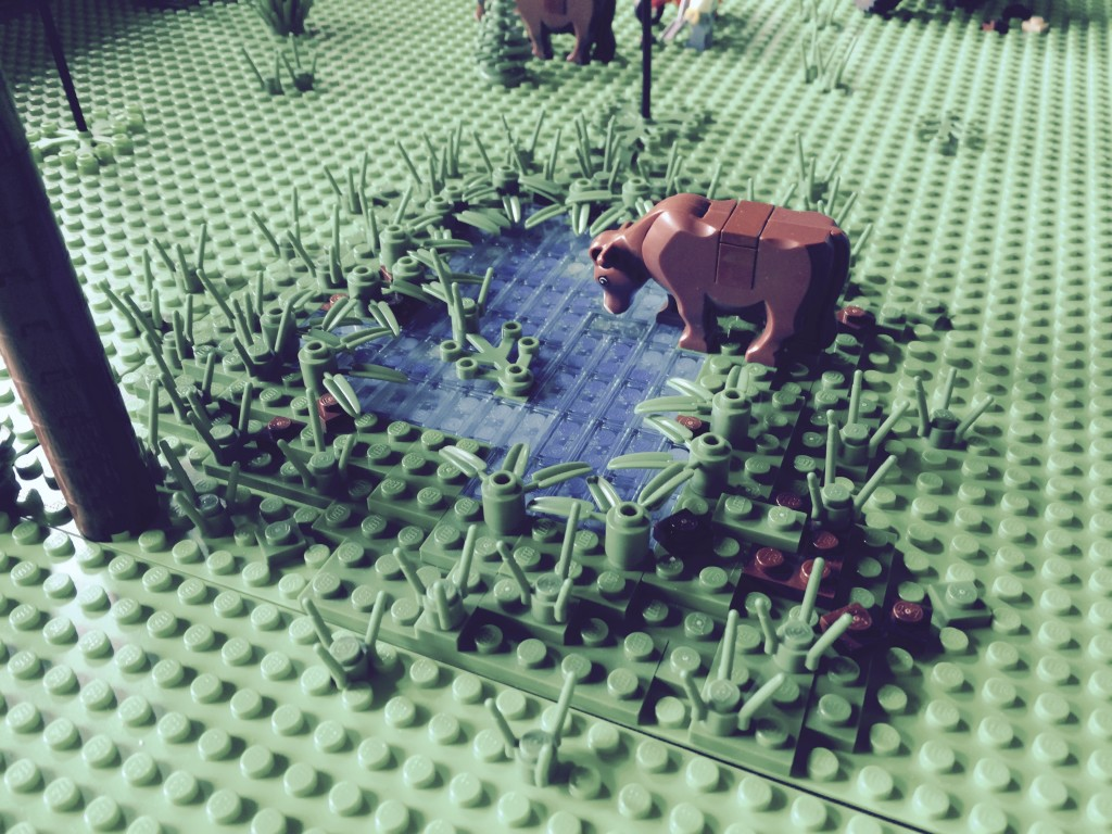 LEGO cow looking at a pond
